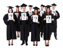 Graduate students holding question signs Royalty Free Stock Image