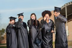 Graduate Students Looking Through Diplomas On Royalty Free Stock Photo