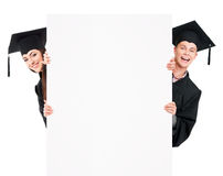 Graduate students. In mantle showing blank placard board, isolated on white background Stock Photography