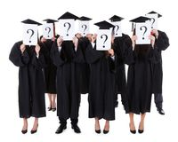 Graduate students showing question signs Stock Photo