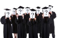 Graduate students showing question signs Stock Images