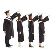 Graduate students standing a row and pointing the same Royalty Free Stock Photography