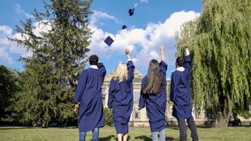 Graduate students throwing square hats up, popular tradition, higher education. Stock photo royalty free stock photo