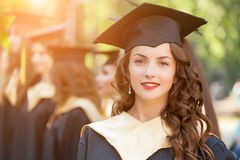 Graduate students wearing graduation hat and gown. Outdoors Royalty Free Stock Photo