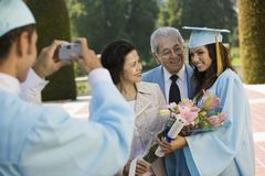 Graduate taking picture of other graduate and grandparents outside Stock Image