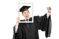 Graduate taking selfie behind a picture frame Royalty Free Stock Images