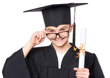 Graduate teen boy student. Portrait of graduate teen boy student in black graduation gown with hat and eyeglasses, holding diploma - isolated on white background Stock Photos