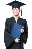 Graduate teen boy student. Portrait of a graduate teen boy student in a black graduation gown with hat, holding certificate - isolated on white background. Child Stock Photo
