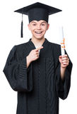 Graduate teen boy student. Portrait of a graduate teen boy student in a black graduation gown with hat, holding diploma - isolated on white background. Child Royalty Free Stock Photo