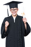 Graduate teen boy student. Portrait of a graduate teen boy student in a black graduation gown with hat, holding diploma - isolated on white background. Lucky Royalty Free Stock Image