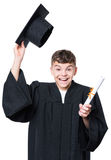 Graduate teen boy student. Portrait of a happy graduate teen boy student in a black graduation gown with hat and diploma - isolated on white background. Lucky Stock Photos