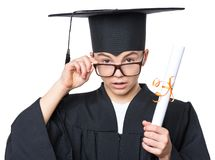 Graduate teen boy student. Portrait of sad or surprised graduate teen boy student in mantle with black hat and eyeglasses, holding diploma - isolated on white Royalty Free Stock Images