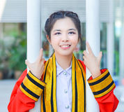 Graduate Thai college girl is is holding poles and Royalty Free Stock Image