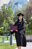 Graduate of university. The girl the graduate of university with the diploma in hands, in park Royalty Free Stock Images
