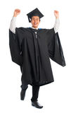 Graduate university student celebrating. Full body excited handsome Asian male university student in graduation gown jumping high, isolated on white background Royalty Free Stock Photo