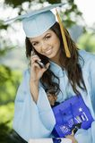 Graduate Using Cell Phone and holding gift bag Royalty Free Stock Image