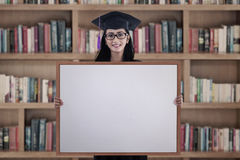 Graduate woman with blank board Royalty Free Stock Photos