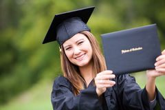 Graduate: Woman Proudly Holding Up Diploma Royalty Free Stock Photography