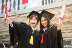 Graduate women students in Commencement day. Asian beautiful young female students with black graduation gowns hold diploma and stand together with modern Royalty Free Stock Image