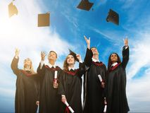 Graduated students throwing hats in the air Royalty Free Stock Image