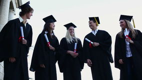 Graduated students throwing up their hats stock video footage