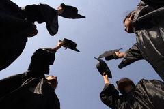 Graduates. Happy graduate girls throughing hats Royalty Free Stock Images