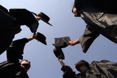 Graduates. Happy graduate girls throughing hats Royalty Free Stock Photos