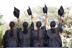 Graduates. Fresh girl graduates holding hats Royalty Free Stock Image