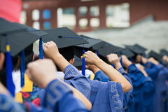 Graduates. Back of graduates put hands up during commencement Royalty Free Stock Photo