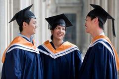 Graduates Chatting. Three young graduates wearing graduation attire chatting in a hallway stock photography