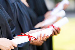 Graduates with diplomas. Royalty Free Stock Photo