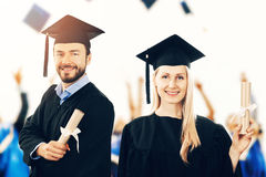 Graduates with diplomas wearing gowns at graduation ceremo Stock Photography