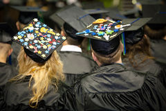 Graduates With Fancy Caps. Students at a graduation ceremony with highly decorated and expressive caps. Men and women listening to the commencement speaker Stock Photography