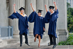 Graduates Fist Pump. Three young graduates pump their fists in the air outdoors and celebrate their achievement Royalty Free Stock Photos