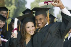 Graduates hoisting diplomas outside Stock Photo