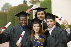 Graduates hoisting diplomas outside portrait Stock Images