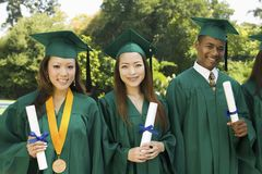 Graduates hoisting diplomas outside university Royalty Free Stock Photography