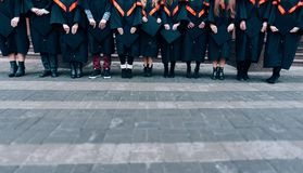 Graduates holding their hats in hands. Graduates wearing robes and hats in their hands. Group of students in bachelor gowns. stock photos