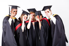 Graduates looking through diploma Stock Photos