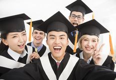 Graduates making selfie photo in classroom Stock Photo