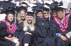 Graduates march across the stadium field Royalty Free Stock Photos