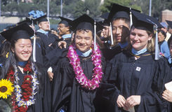 Graduates march across the stadium field Royalty Free Stock Images