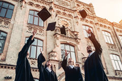 Graduates near university. Are throwing up hats in the air stock image