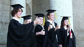 Graduates posing the thumbsup stock video