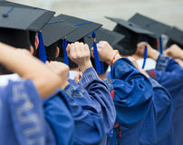 Graduates put hands up. Back of graduates put hands up during commencement Royalty Free Stock Photo