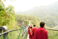 Graduates on suspension bridge Stock Photo
