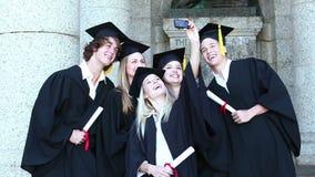 Graduates take self portrait together stock footage