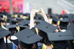 Graduates. Taking photos by cellphone during commencement Stock Photo