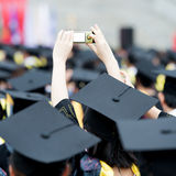 Graduates taking photos. By cellphone during commencement Stock Photos