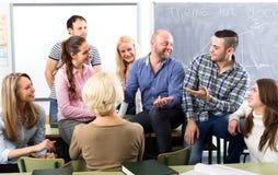 Graduates talking in a classroom Stock Image